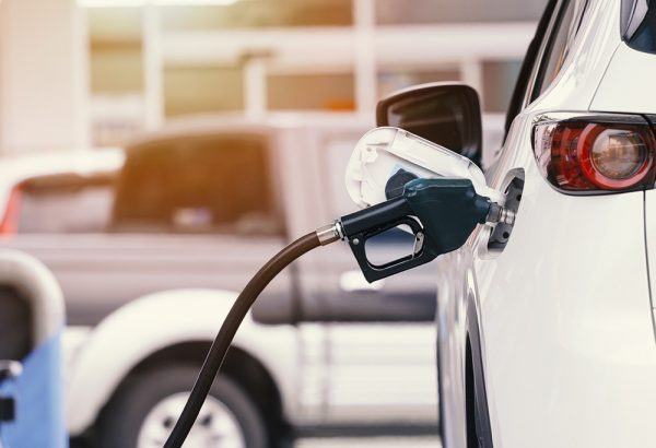 Close up of fuel monitoring system refueling a petroleum to vehicle at gas station.
